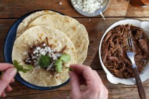 A person assembling a slow cooker barbacoa taco with a pot of shredded barbacoa meat, a small dish of onions, a bottle of hot sauce, and some cilantro around the taco plate.