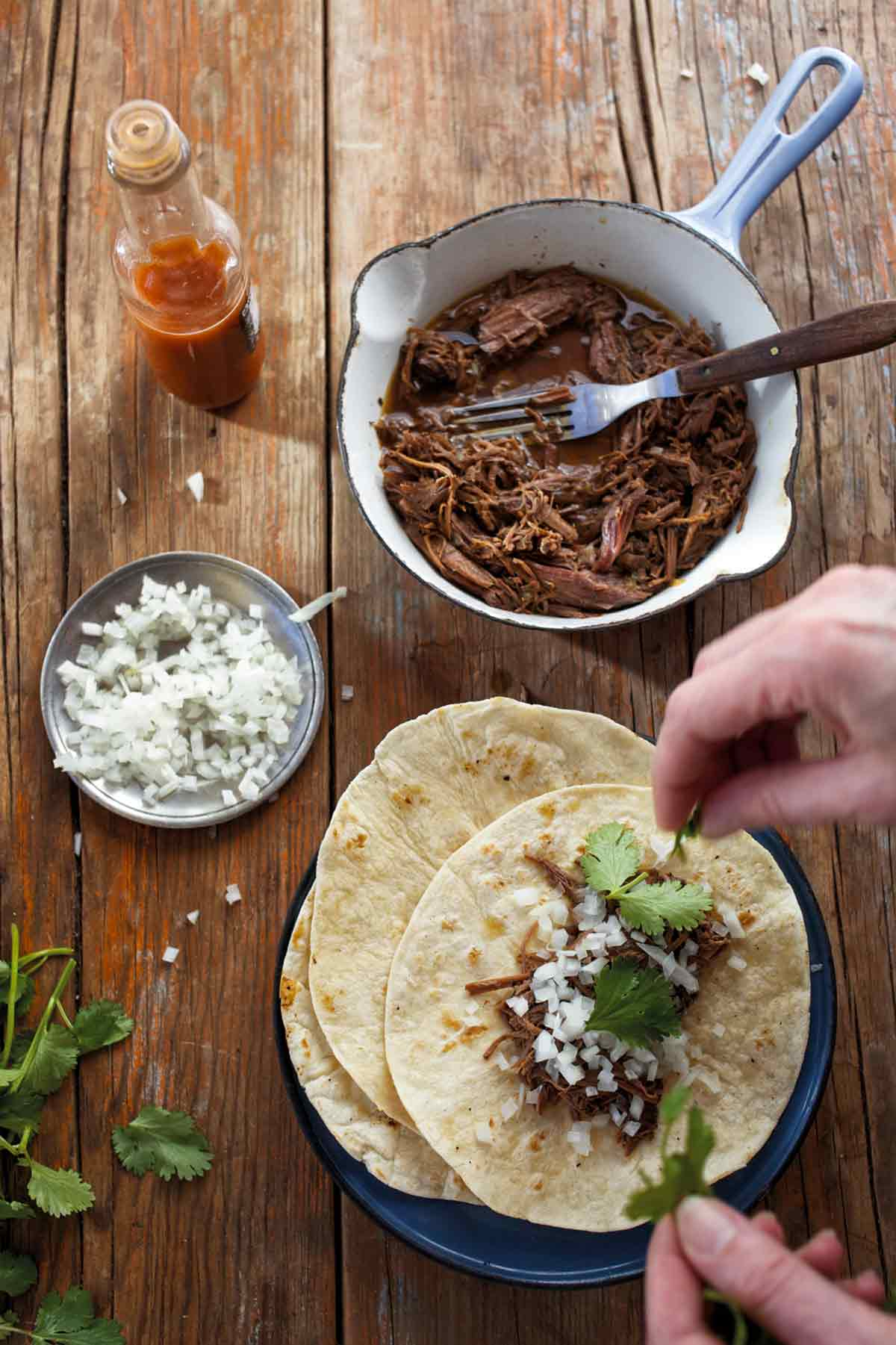 A person assembling a barbacoa taco with a pot of shredded barbacoa meat, a small dish of onions, a bottle of hot sauce, and some cilantro around the taco plate.