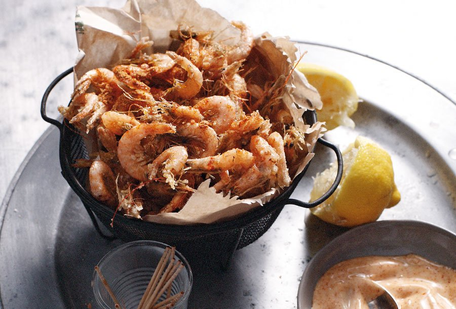 A basket of spiced shrimp with a bowl of paprika mayonnaise beside the shrimp, a halved lemon, and a cup of toothpicks.