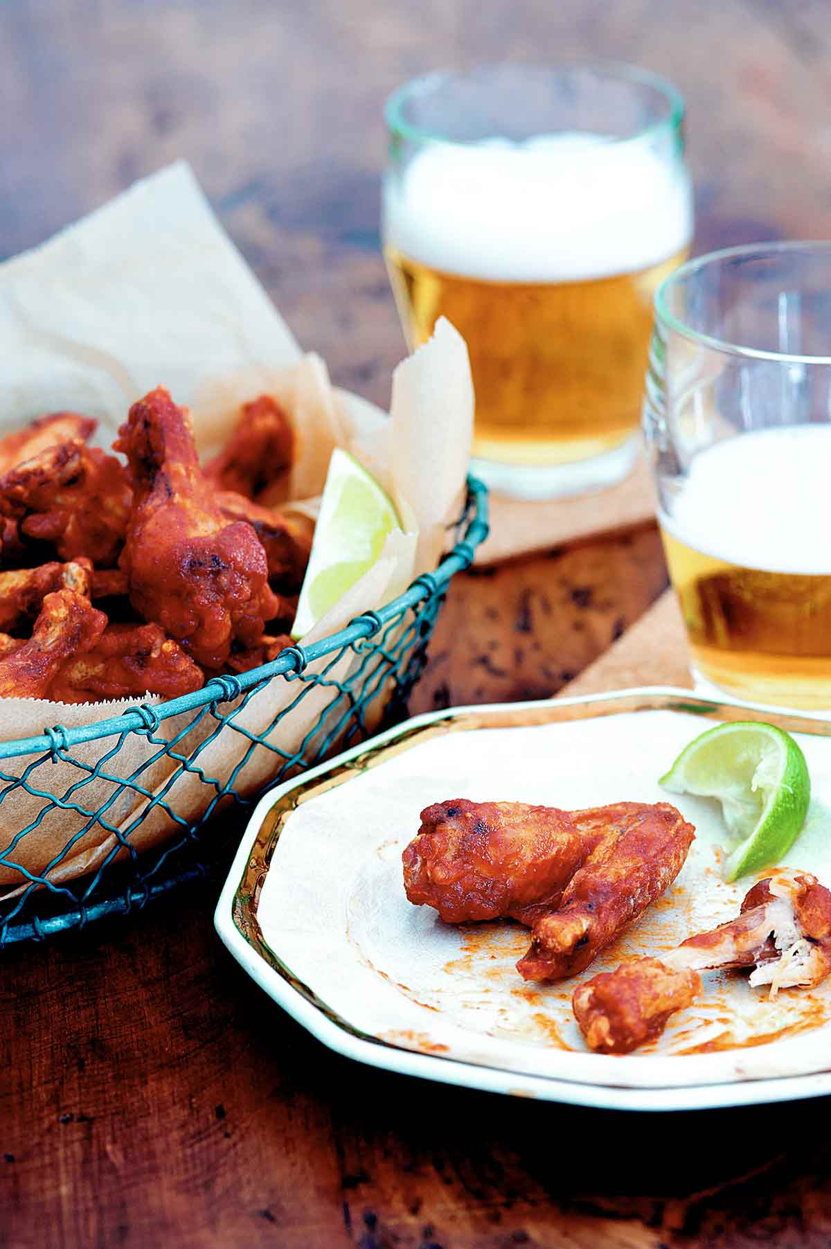 A basket of Sriracha chicken wings, two glasses of beer, and a plate with one eaten and one uneaten chicken wing and a wedge of lime.