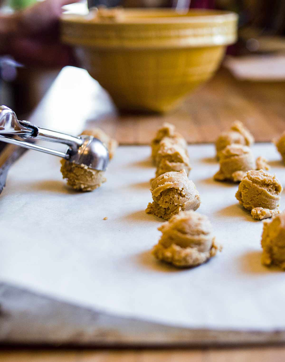 Rows of peanut butter sandies dough balls with a cookie scoop placing another dough ball on the surface.