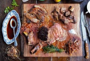 A medium-rare rib roast deboned and sliced into pieces on top of a wooden cutting board