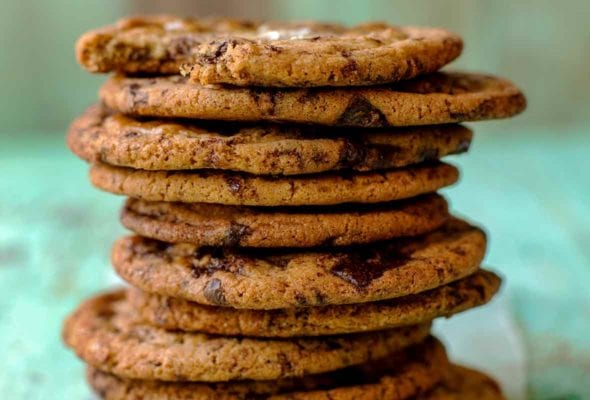 Stack of 10 chocolate chip cookies, each topped with sea salt on an aqua piece of wood