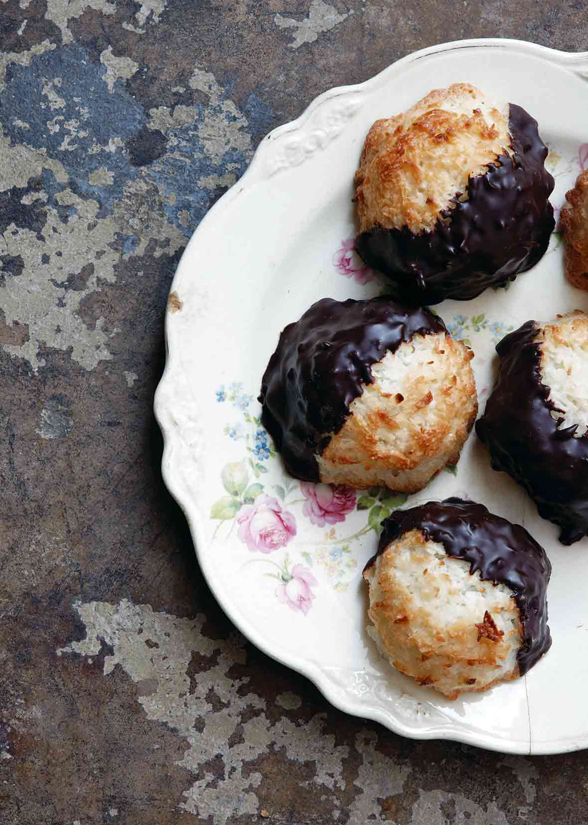 Five coconut macaroons dipped in chocolate arranged on a floral-patterned china plate.