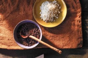 A bowl of Cuban black bean soup with a wooden ladle next to a yellow plate filled with white rice.