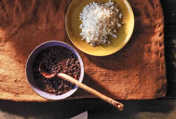 A bowl of black bean soup with a wooden ladle next to a yellow plate filled with white rice.