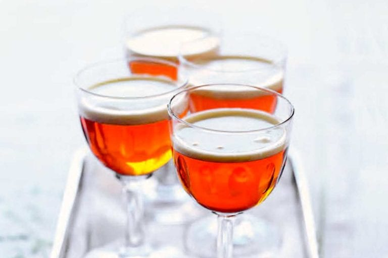Four aperitif glasses filled with little hot after dinner shots on a silver tray.