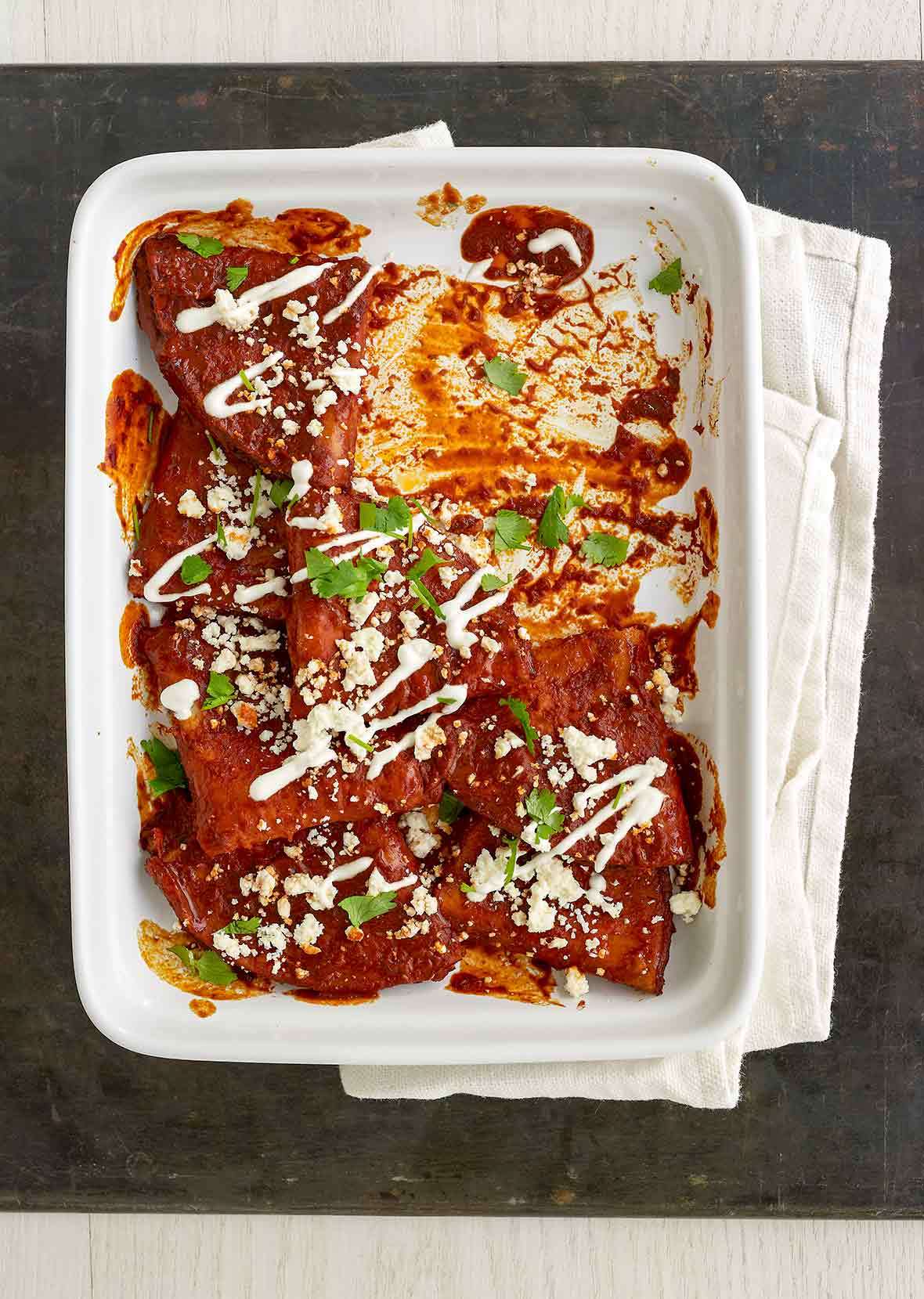 White casserole dish with cheese enchiladas, red sauce, sour cream, crumbled cotija cheese, and chopped cilantro