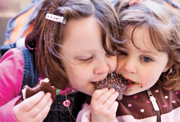 Two girls sharing a chocolate cookie decorated with sprinkles.