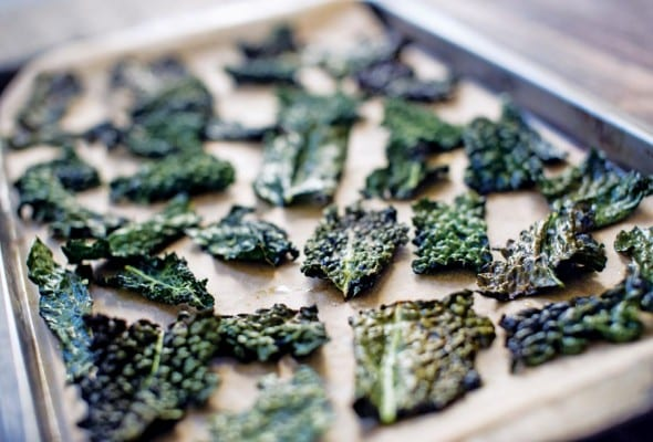 A rimmed baking sheet filled with crispy baked kale chips.