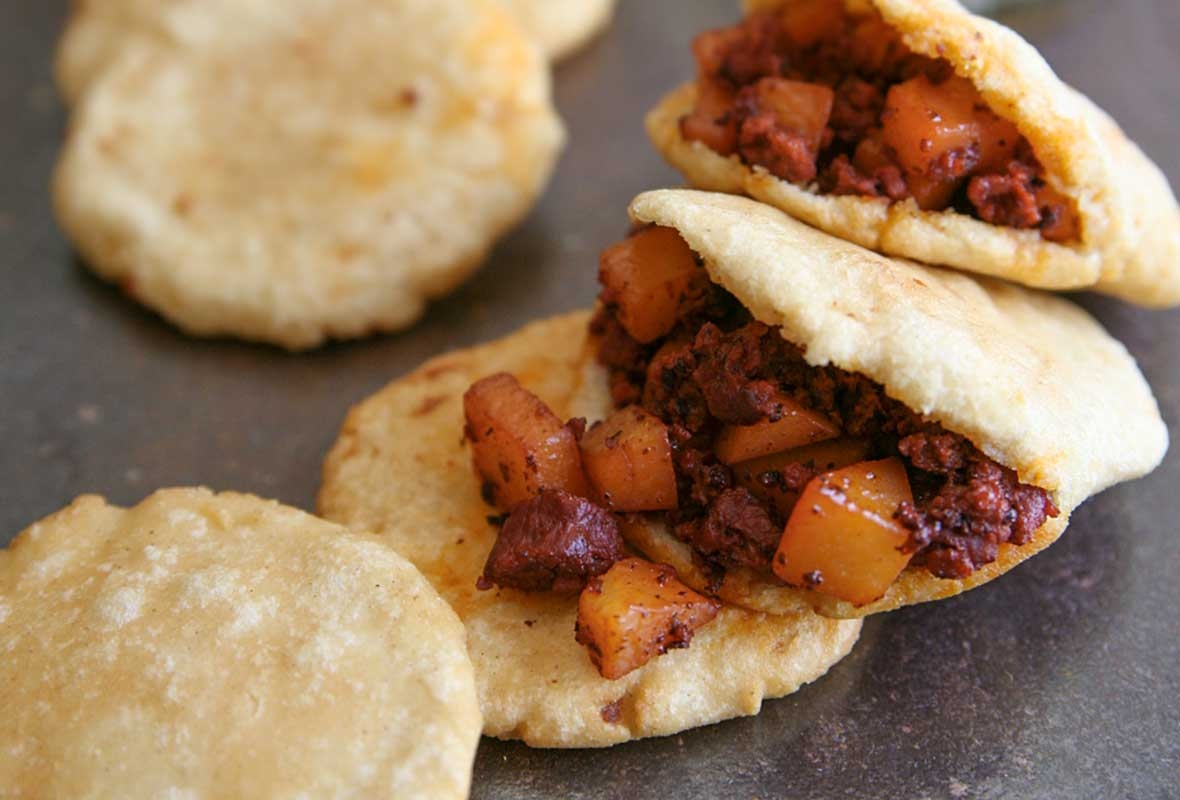 Potatoes with Mexican chorizo stuffed into pitas with a glass of beer in the background.