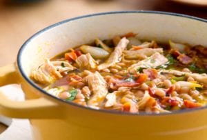 A yellow Dutch oven filled with white bean and chicken chili, topped with pieces of bacon.