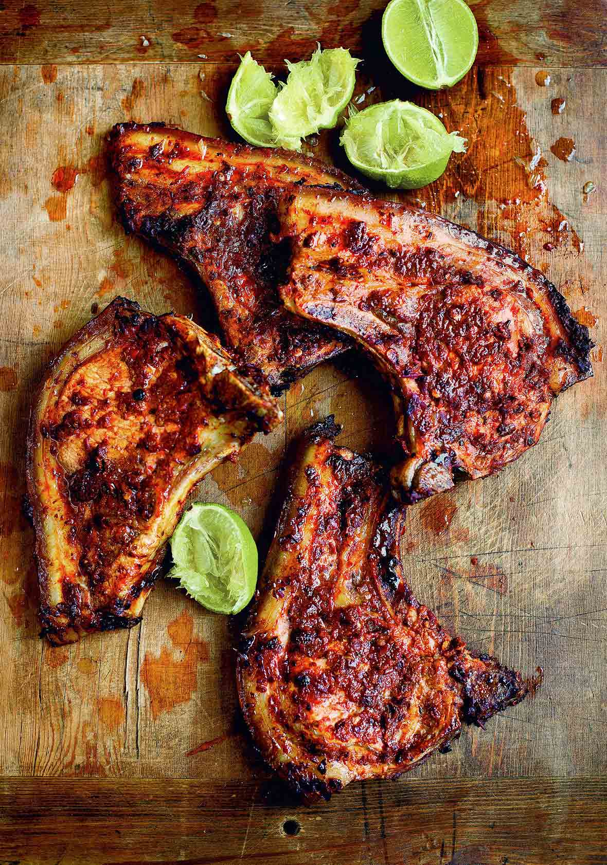 Four adobo marinated pork chops and several lime halves, some squeezed, on a wooden chopping block.
