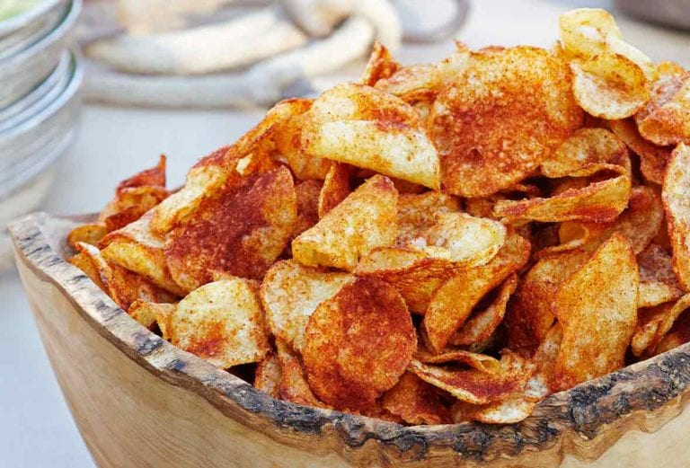 A carved wooden bowl filled with barbecue potato chips.