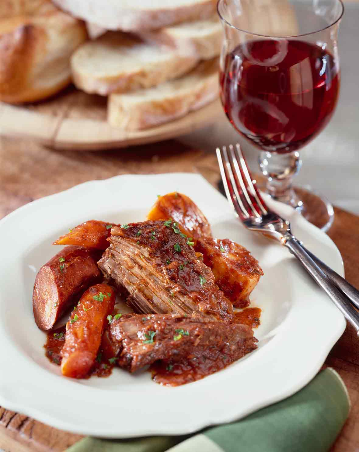A white bowl with carne assada--braised beef with carrots, potatoes, and Portuguese sausage, chouriço