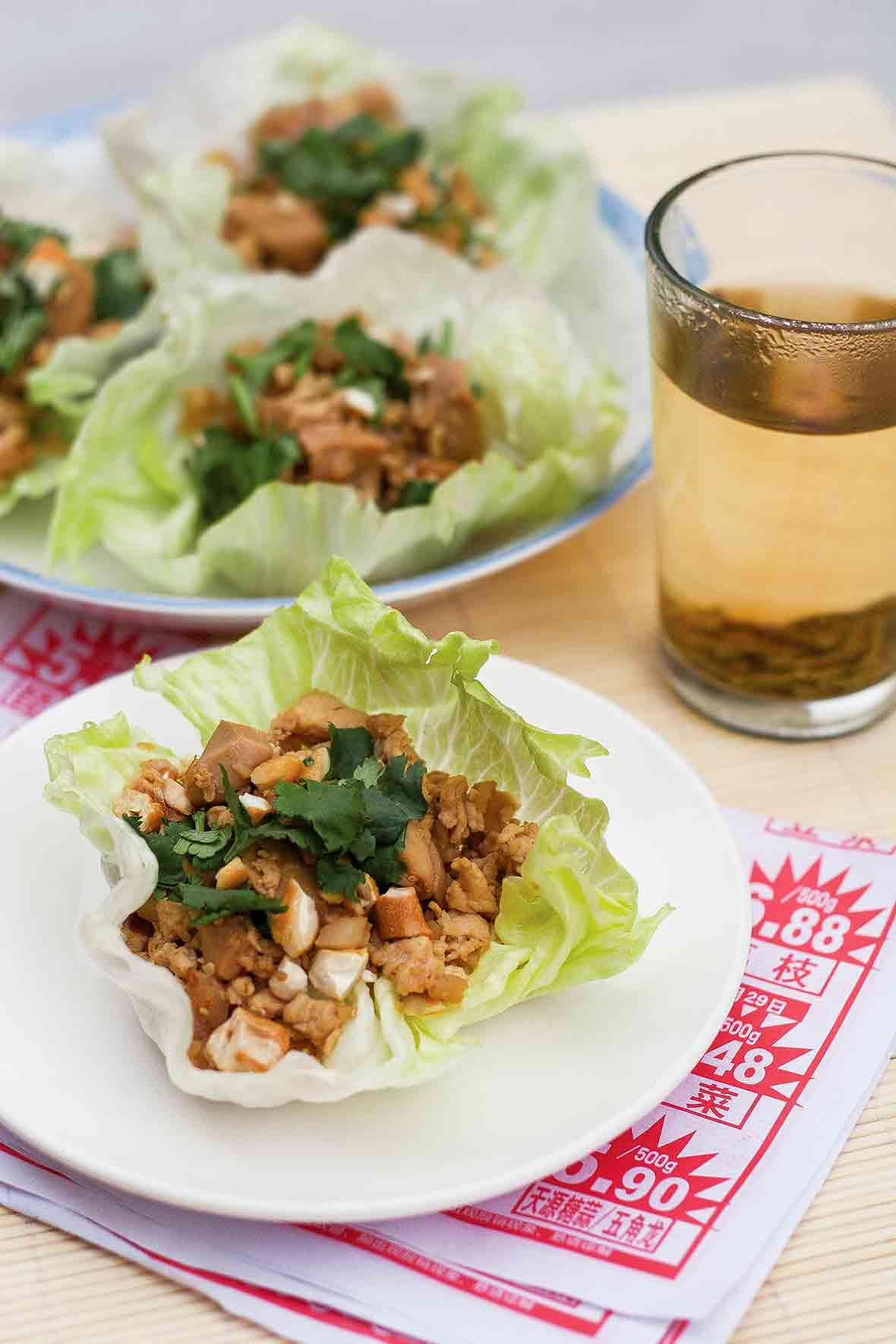 A Chinese chicken lettuce cup topped with cashews and cilantro on a white plate.