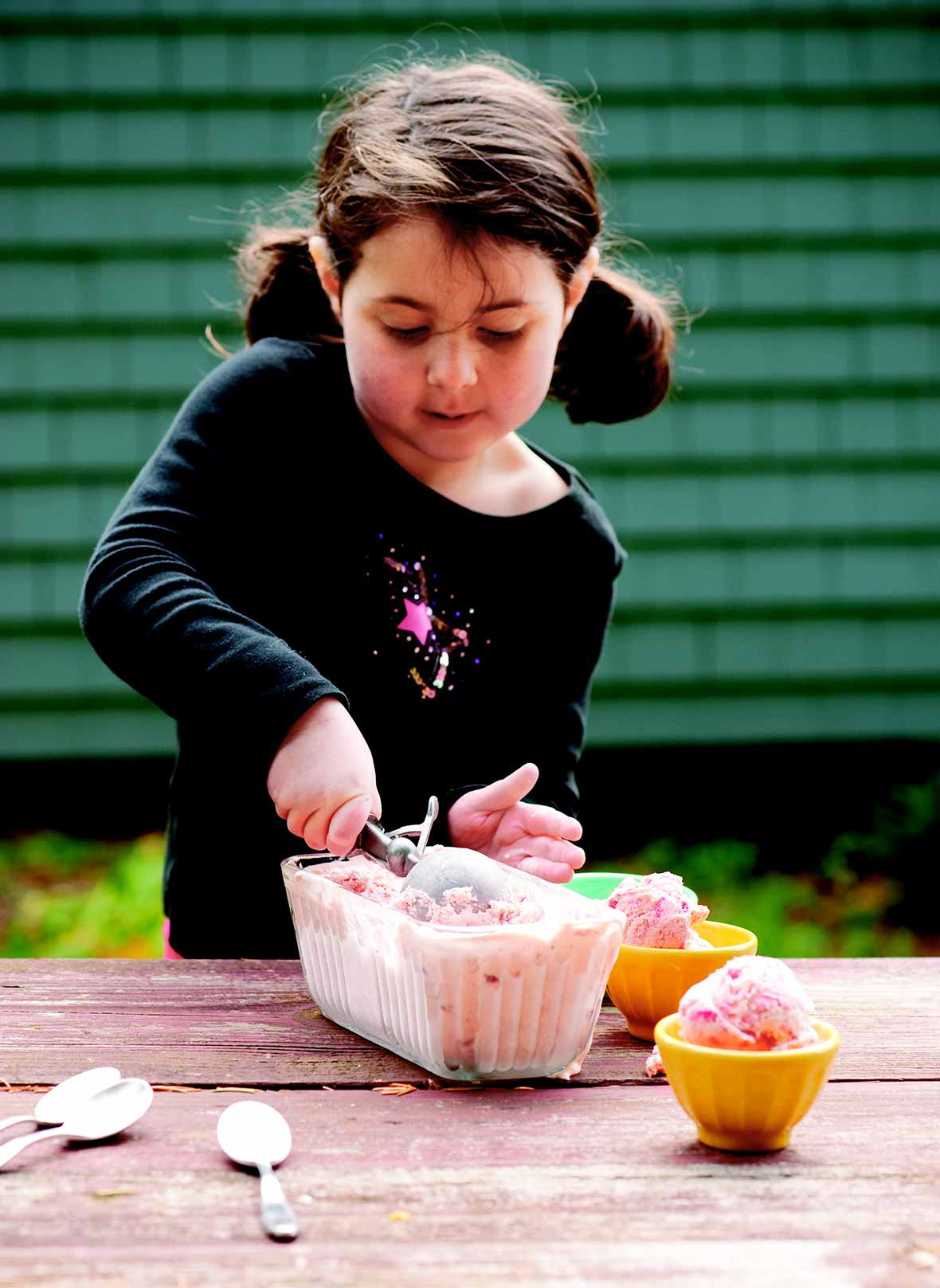 A little girl scooping strawberry ice cream into bowls.