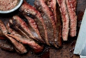 A sliced grilled flank steak with a bowl of seasoning mix and a knife on the side.