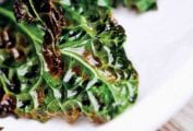 Leaves of grilled kale, coated with olive oil, on a white platter.