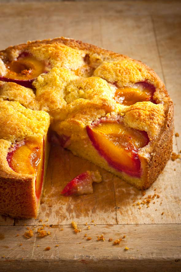 A round polenta plum cake on a wooden table with one slice cut from it.