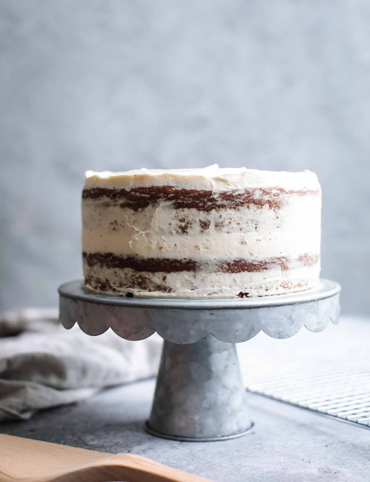 A double layer cake on a cake stand frosted in white chocolate-cream cheese frosting