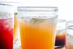 A glass filled with cantaloupe agua fresca, and glasses of other liquid around it.