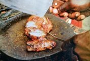 A sliced jerk chicken breast on a round cutting board, with a man's hand holding a cleaver above it