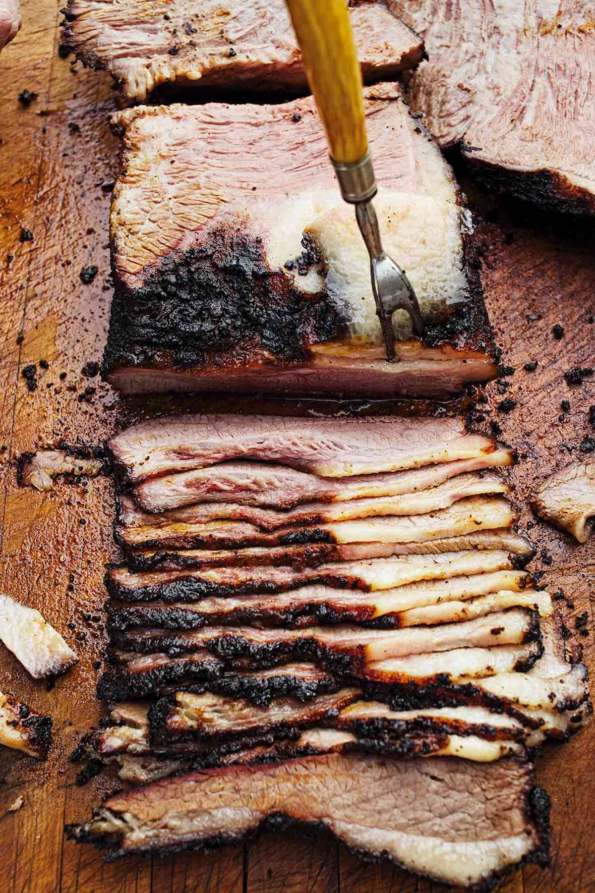 A slab of deeply smoked barbecue beef brisket being sliced on a cutting board