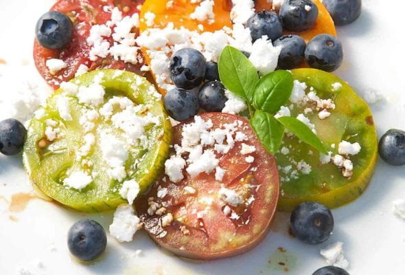 Sliced tomatoes with blueberries and crumbled feta scattered on top and a sprig of basil for garnish.