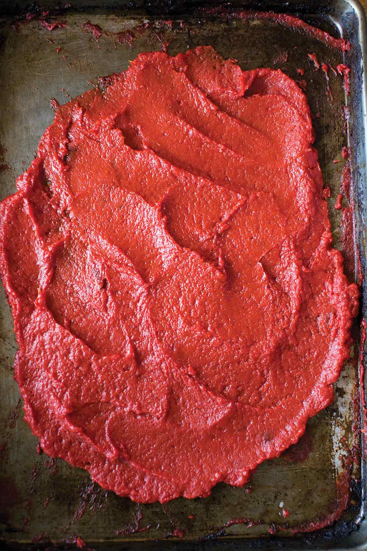 A rimmed baking sheet spread with a thick layer of homemade tomato paste.