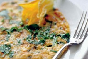 An Italian frittata garnished with a squash blossom on a white plate with a fork resting beside it.