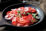 A wooden serving plate filled with sliced tomatoes, red onion, and chopped cilantro.