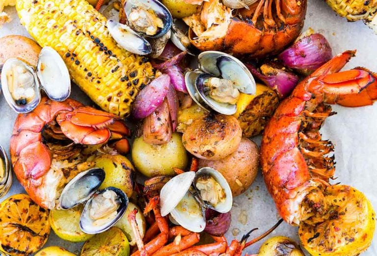 All the fixings for a New England clambake - lobster, clams, potatoes, corn, lemon - scattered on a white surface.