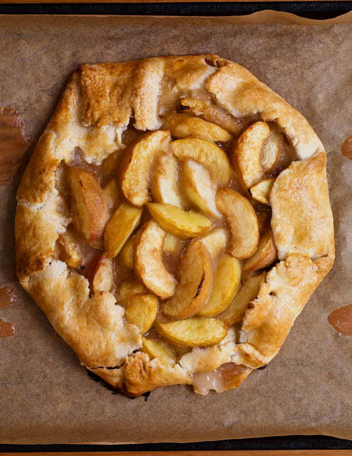 A white peach crostata--slices of white peaches in a circle of dough folded over on the edges sitting a sheet of parchment