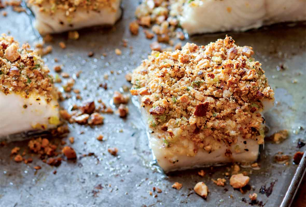 Four fillets of baked fish with almonds, lemon, and bread crumbs on a rimmed baking sheet.