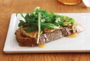 A slice of bread topped with peanut butter, honey, and arugula on a white plate.