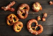 Soft pretzels of assorted shapes and sizes on a wooden surface.