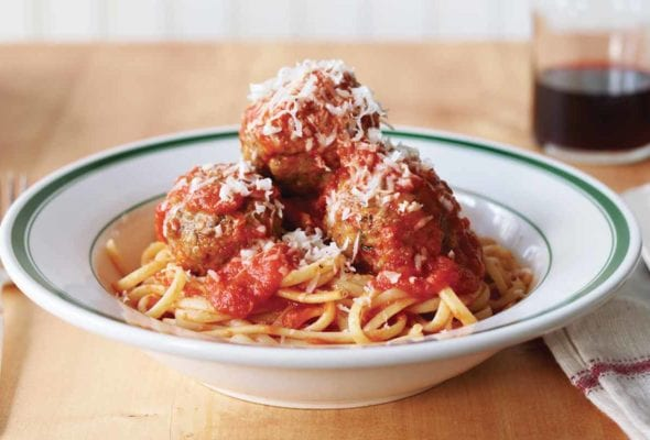 Three classic beef meatballs piled on pasta in a white and green bowl an finished with Parmesan.