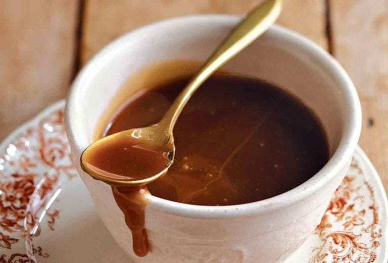 Easy caramel sauce in a teacup on a patterned saucer with a gold spoon resting on top and some caramel dripping down the side of the cup.