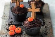 Three graveyard Halloween cupcakes with mini pumpkin candies and crosses on a piece of slate.