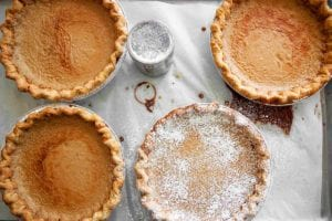 Four Hoosier sugar cream pies, one dusted with confectioners' sugar on a sheet of parchment.