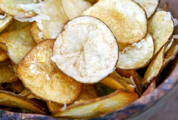 A wooden bowl filled with Manchego potato chips and sprinkled with more Manchego cheese.
