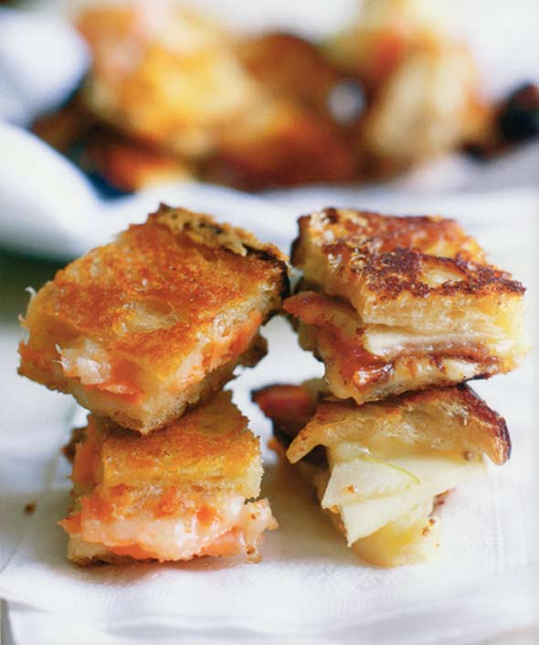Four pieces of Cheddar, bacon, apple grilled cheese sandwiches stacked on top of each other.