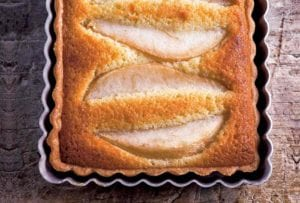 A pear almond tart in a rectangular tart pan on a wooden board.