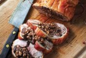 A roast duck stuffed with farro, figs, and hazelnuts, with three slices cut from it on a wooden cutting board with a knife resting beside it.