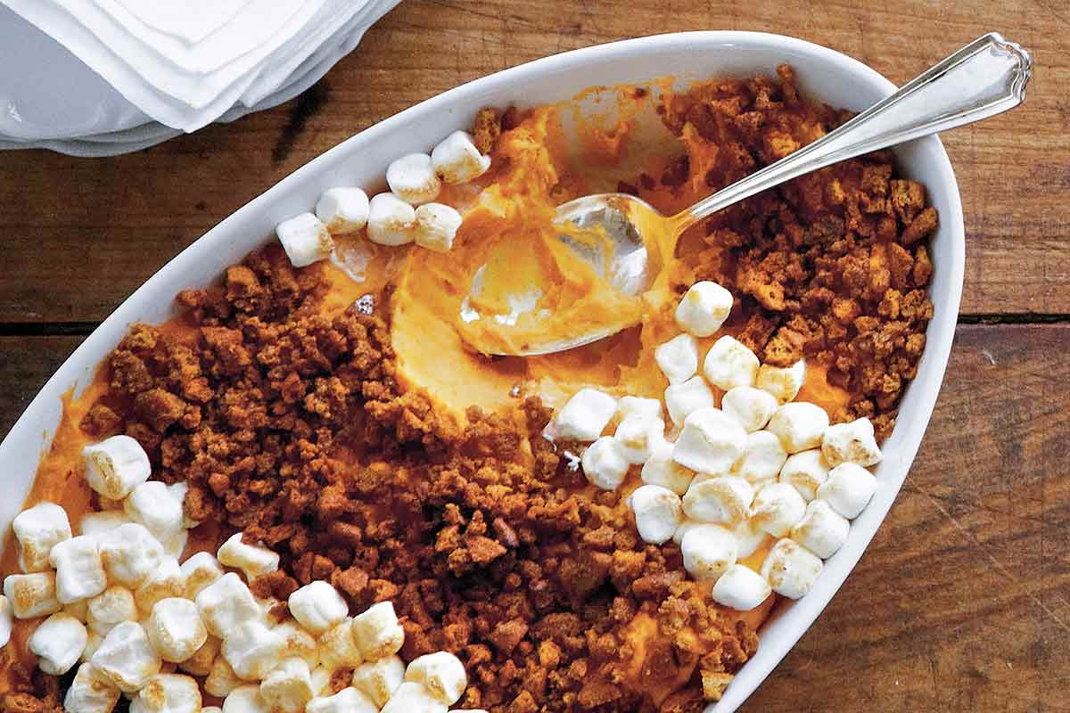 A white casserole dish filled with gingersnap and sweet potato casserole, topped with mini marshmallows and a spoon resting inside.