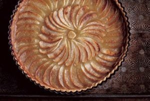 A round tart filled with cooked sliced apples in a concentric pattern