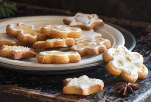 A white plate with a pile of sugar cookies coated in a champagne glaze.