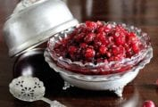 A silver and glass decorative dish filled with Raw Cranberry Sauce. A lid for the dish and a silver spoon rest beside the dish.