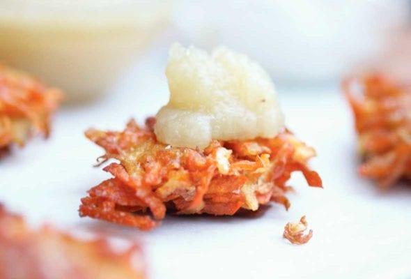A root vegetable latke topped with a dollop of applesauce.